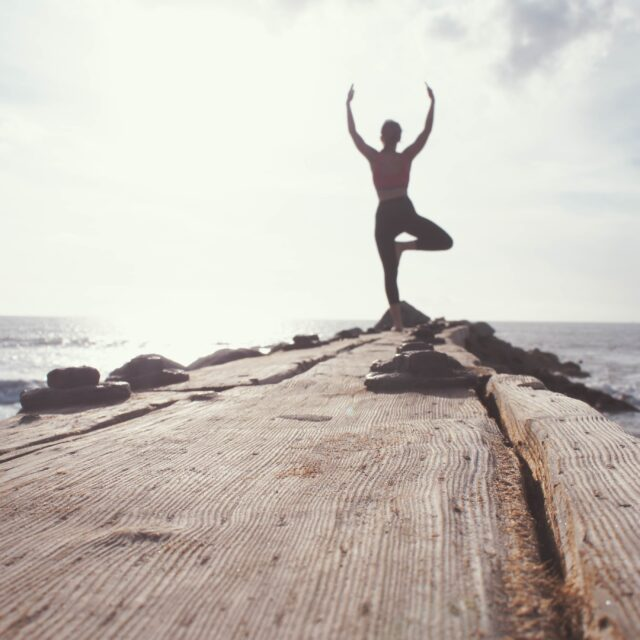 A person doing yoga by the ocean