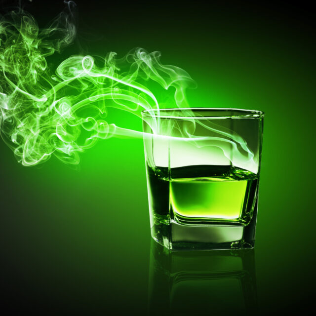 an etheric photo of a glass of alcohol with spirits rising from it